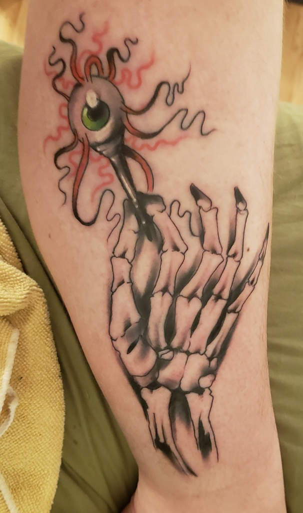 A skeleton hand holds a golf puck between two fingers. A zombie eye, with entrails of blood, sits on top of the puck.